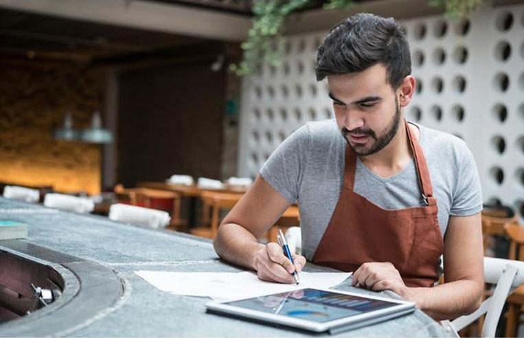 Restaurant owner reviewing merchant insights and analytics on tablet