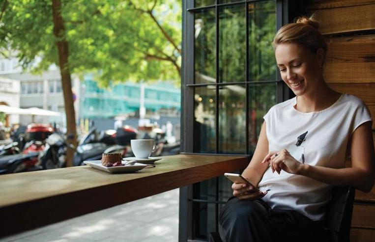 Woman at coffee shop reading mobile device with payment transactions from enterprise merchant solutions