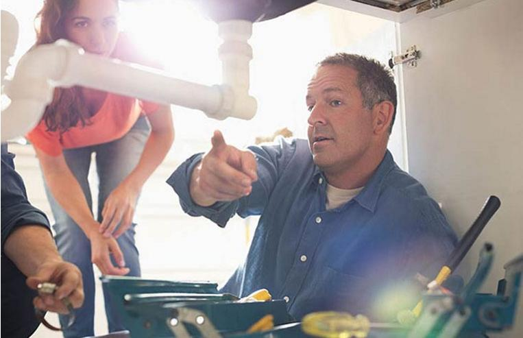 Plumber working under sink can use Bank of America Merchant Services mobile POS solutions