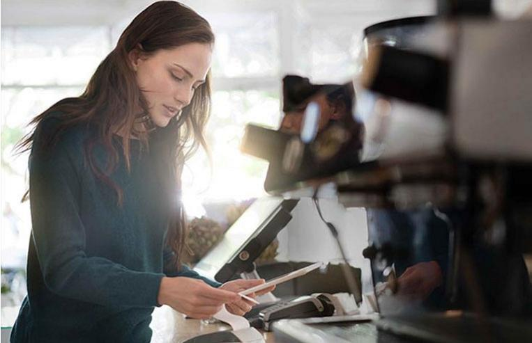 Woman using Clover POS payment processing at coffee shop