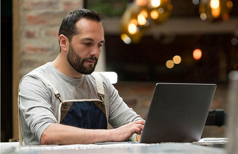 Man working at laptop while reviewing Clover dashboard
