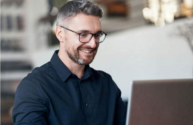 Man smiling while reviewing Business Track web-based reporting tools on a laptop