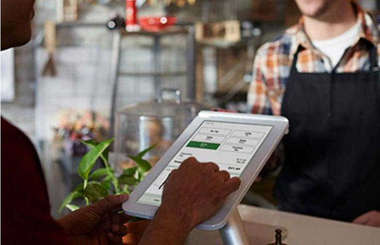 Small business owner accepting payment from customer with Clover Station by Bank of America Merchant Services