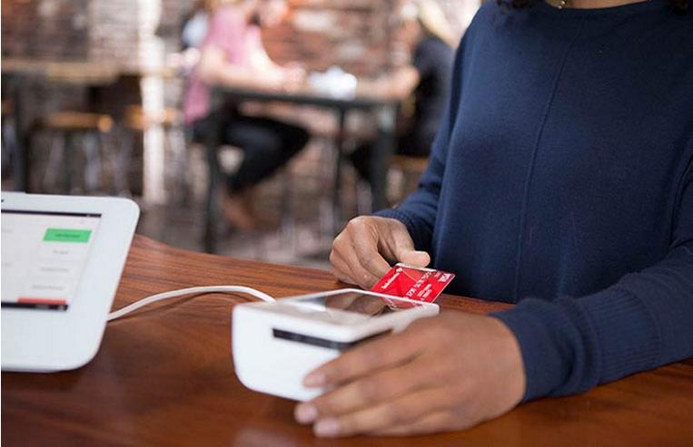 Woman using credit card on a Clover Mini from Bank of America Merchant Services