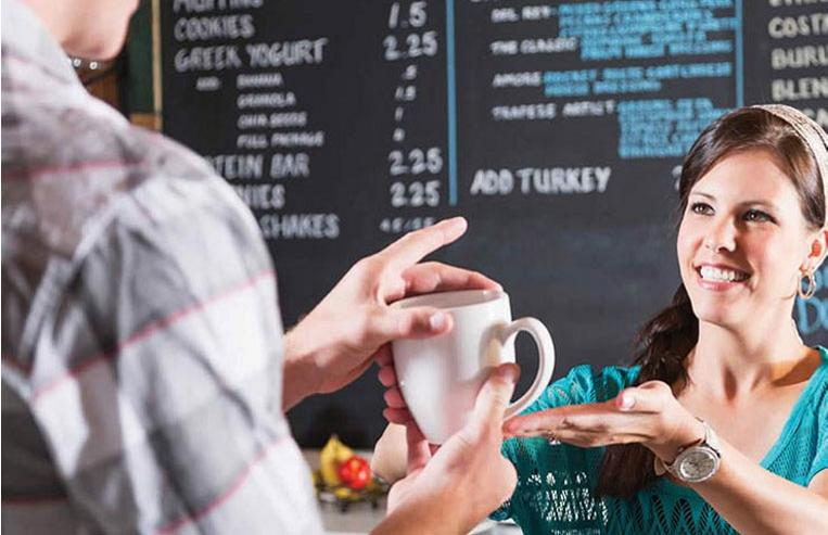 Female barista handing coffee cup to customer