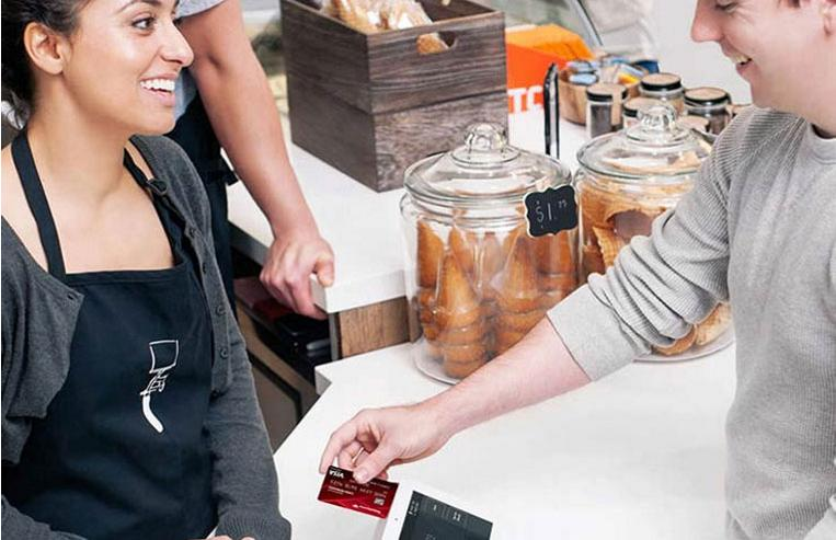 Man paying with a credit card on a Clover Point-of-Sale station at a restaurant