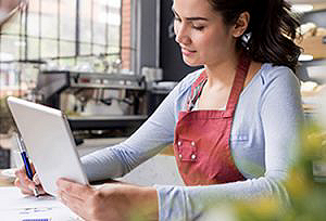 Woman wearing apron taking notes and reading about Small Business Payment Solutions on a tablet device