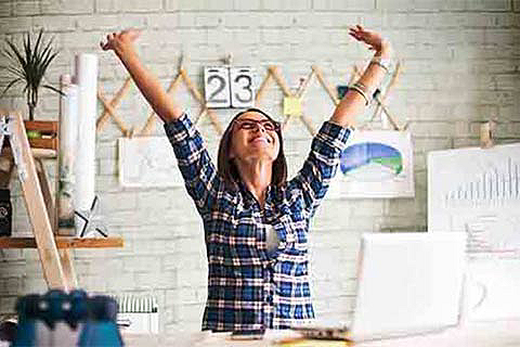 Woman raising hands in excitement about Bank of America Merchant Services Small Business Solutions in her creative studio