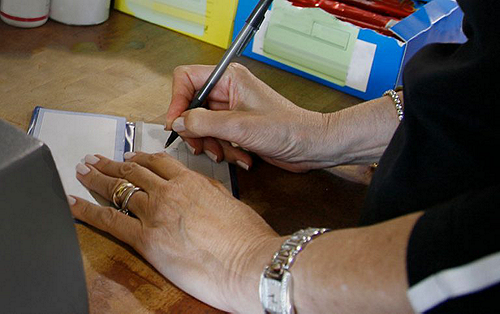 Woman signing check at a store with Clover Check Acceptance to minimize fraud