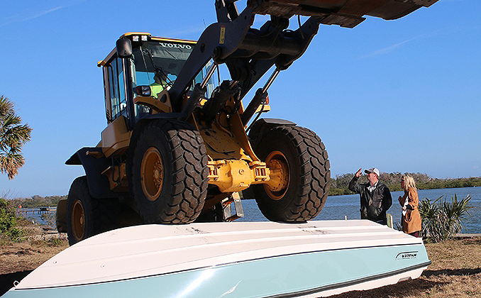 A forklift driving over a Boston Whaler model