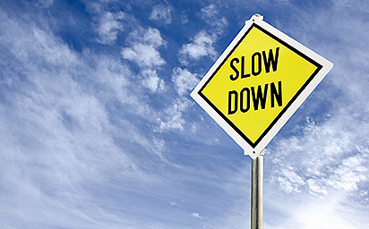 Slow Down yellow road sign against blue sky and clouds
