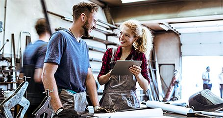 Female small business owner talking with employee at workshop
