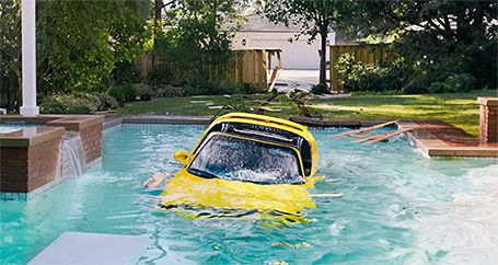Car submerged in swimming pool in backyard of home