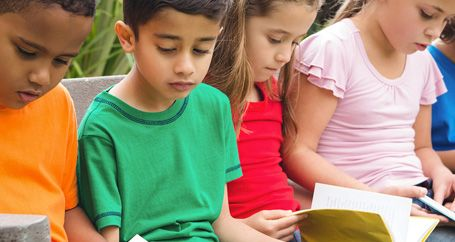 School children reading books outside