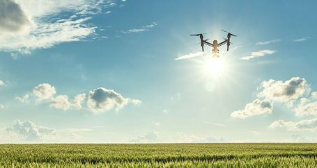 Drone flying with video camera over farmland