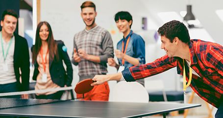 Employees playing ping pong at work