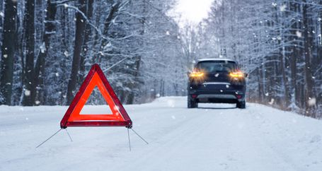 Red hazard triangle on snowy road behind stopped car with emergency flashers on