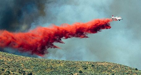 Airplane dropping trail of fire retardant on wildfire