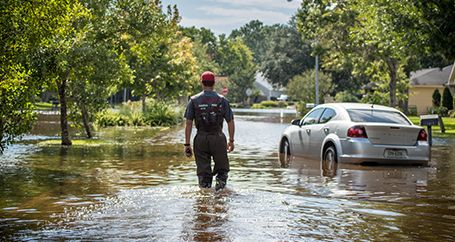 Male first responder approaching car stranded in flooded neighborhood