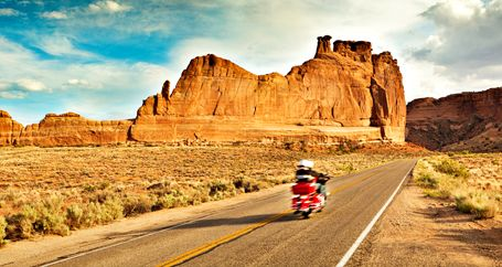 Couple on motorcycle riding through desert