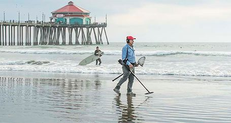 Man looking for lost rings on beach with metal detector