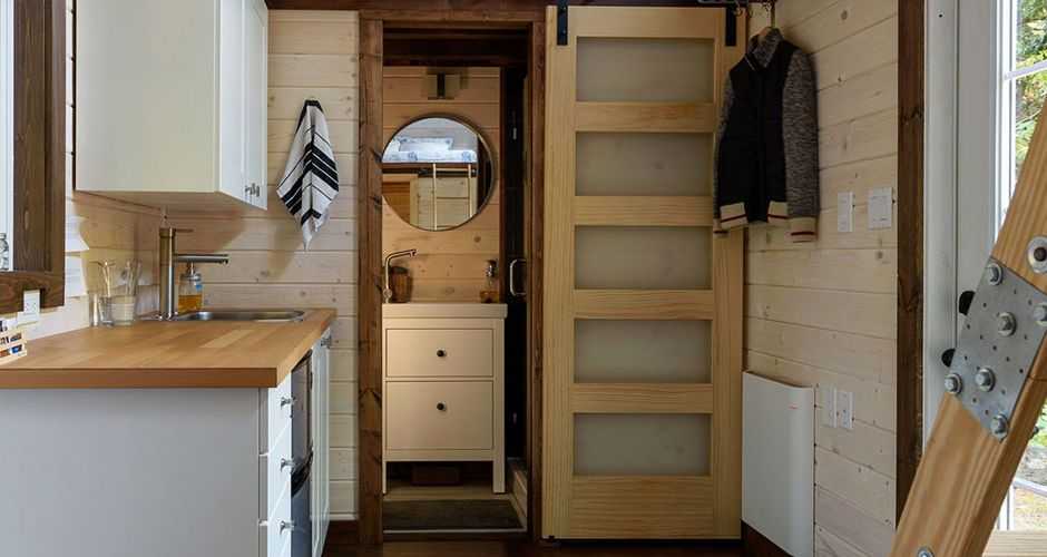 Tiny house interior with wood paneling and loft