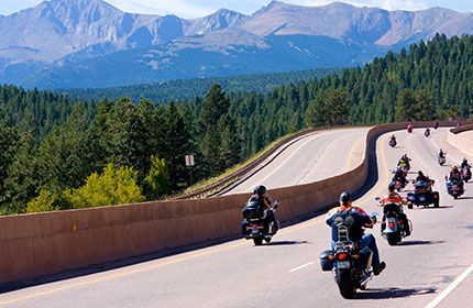 Motorcycle club riding on road surrounded by trees and mountains