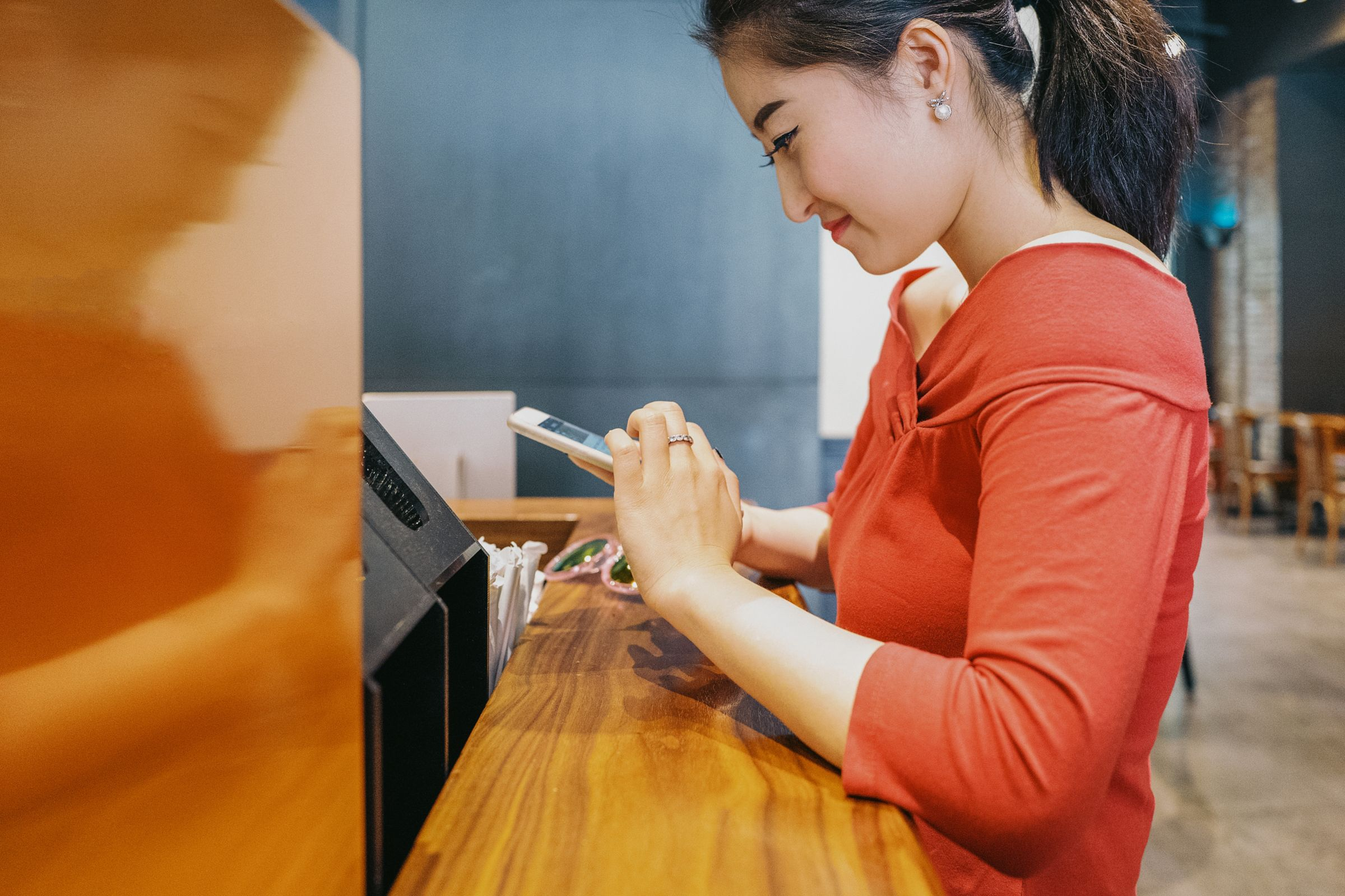 woman at counter holding a phone