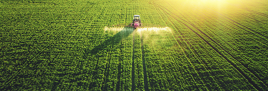 Tractor spraying insecticide on crops