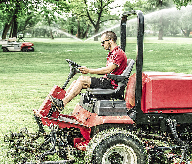 Grounds maintenance worker  on riding lawn mower