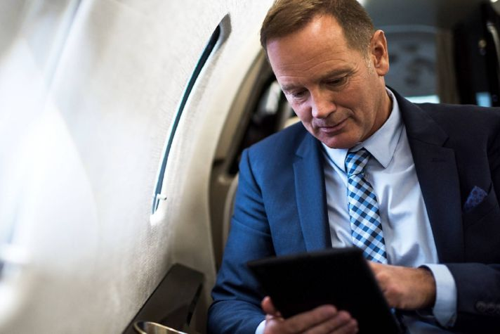 Elegant senior man sitting inside private jet airplane and holding digital tablet.