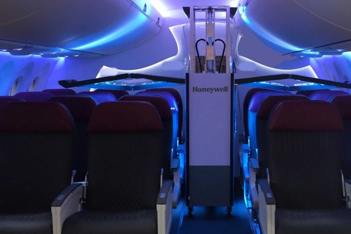 Honeywell UV Cabin System in airplane cabin aisle with arms extended over seating