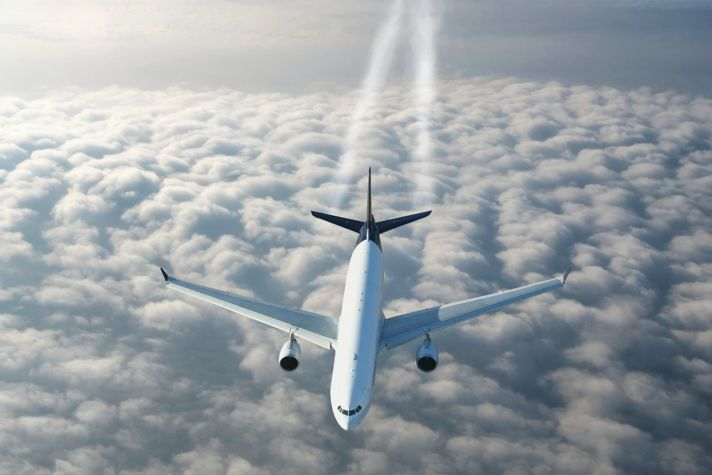 Airplane Flying Over The Clouds