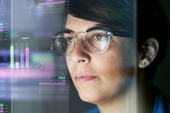 woman looking at data on monitors