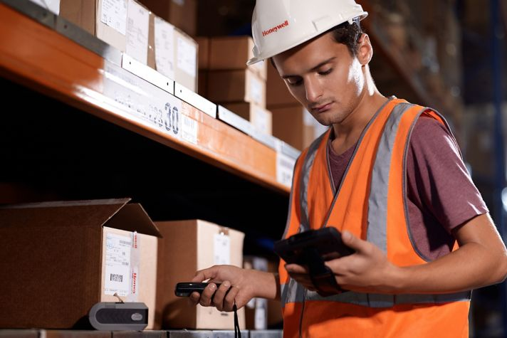 worker between shelves holding a mobile device