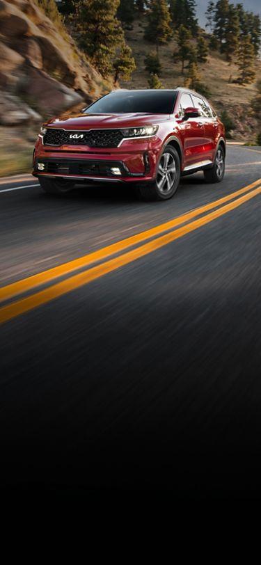 2022 Kia Sorento Hybrid Driving Near Mountains Three-Quarter View