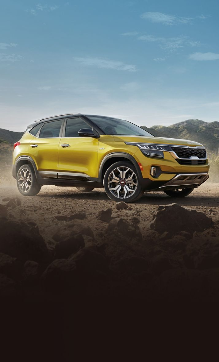2022 Kia Seltos Parked Off Road In Front Of Mountains Three-Quarter View