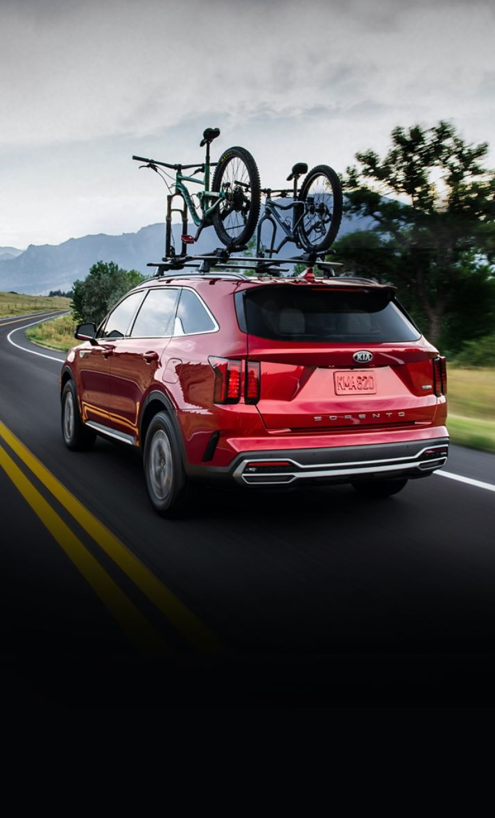2021 Kia Sorento Hybrid Driving Down A Winding Road With A Bike Rack Equipped Rear Three-Quarter View