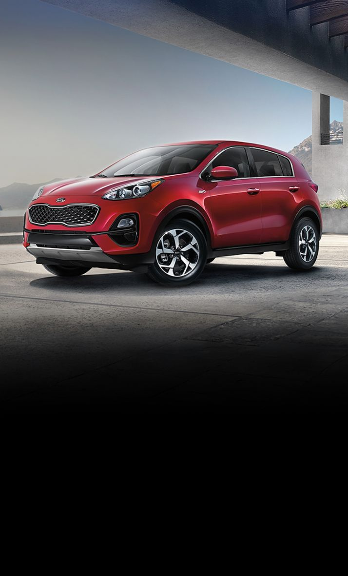 2022 Kia Sportage Parked In Front Of Mountains And A Lake Three-Quarter View