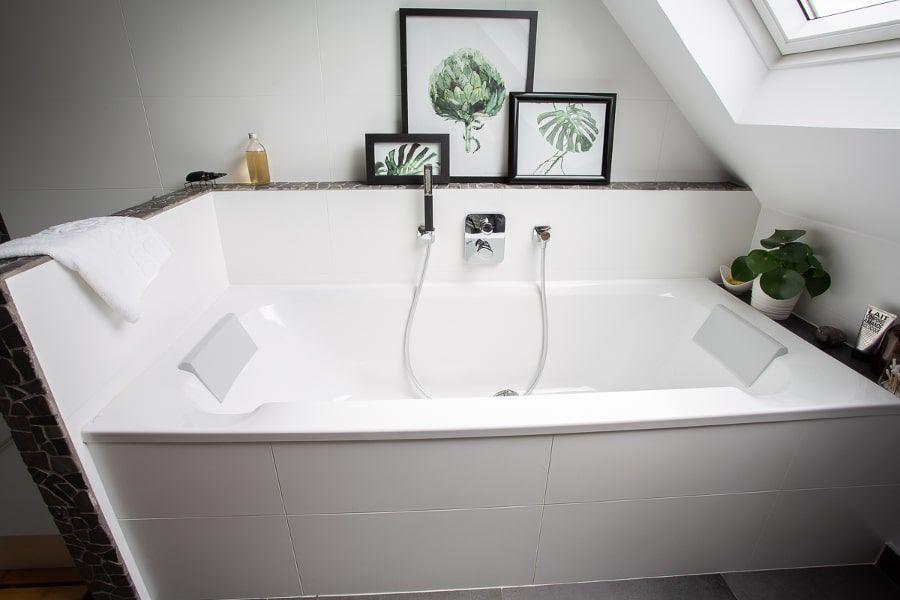 Une grande baignoire immaculée accessoirisée de cadres photos posés sur le rebord