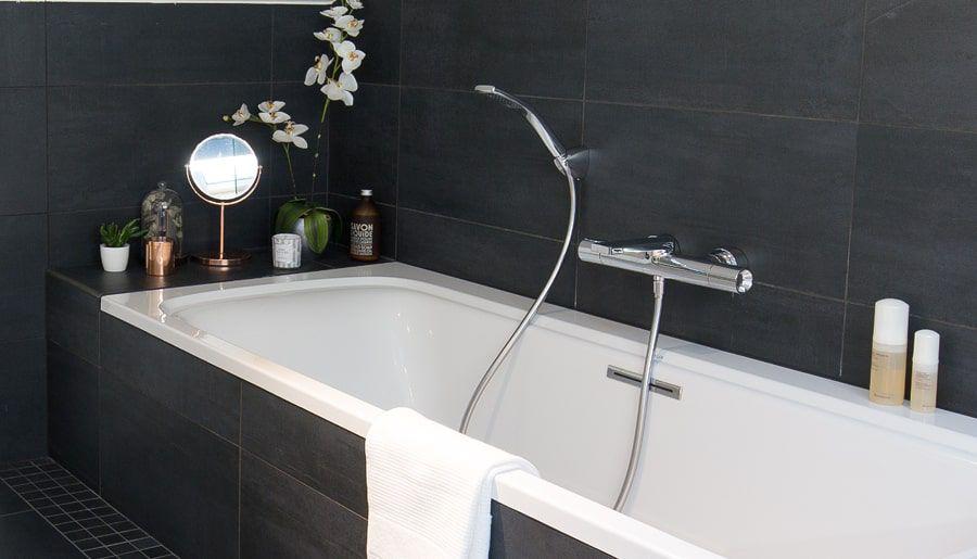 Une grande baignoire dans une salle de bains accessoirisée de décoration et d'un pot de fleur