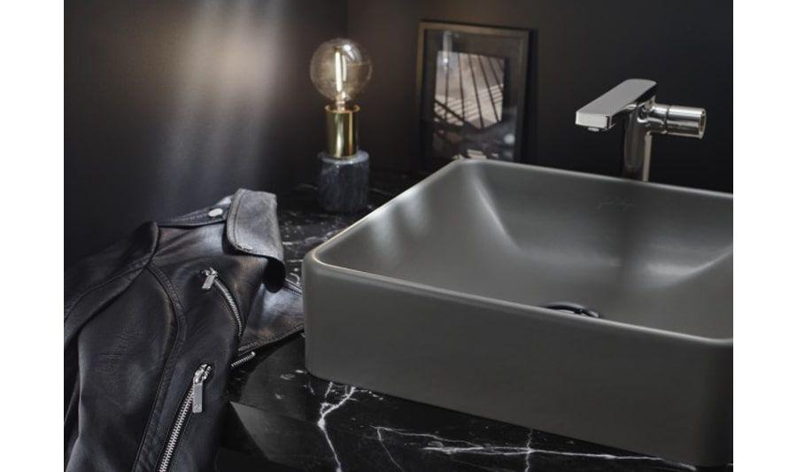 Une vasque à poser gris orage sur un plan de toilette en marbre noir veiné de blanc et une veste en cuir posée dessus