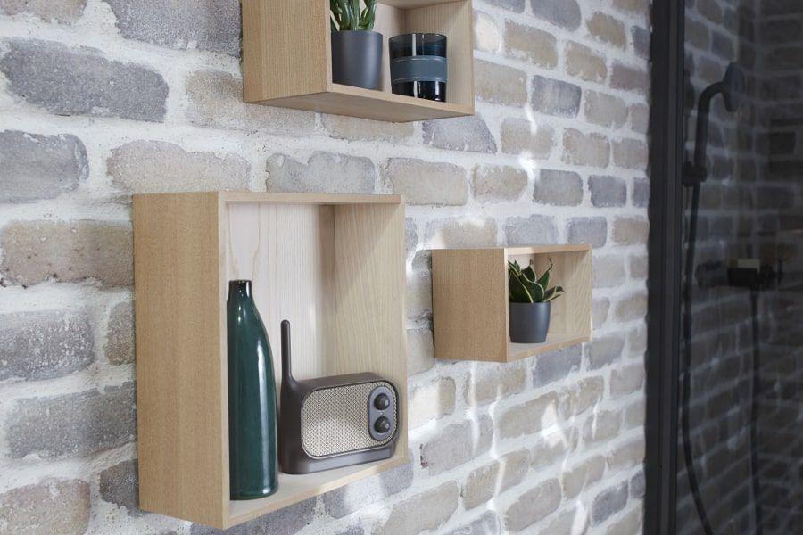 3 casiers en bois contenant des accessoires déco fixés sur un mur en pierre