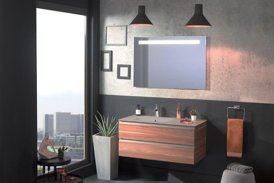 Une salle de bains au style industriel avec un grand meuble vasque couleur terra cotta et des suspensions noires