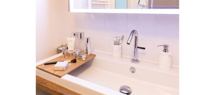 Des accessoires de bains et du maquillage posés sur une vasque avec tablette en bois amovible