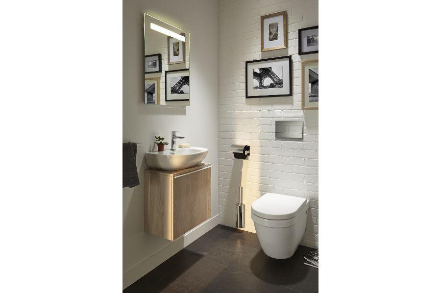 Des toilettes avec un meuble lave-mains en bois et des murs carrelés blancs