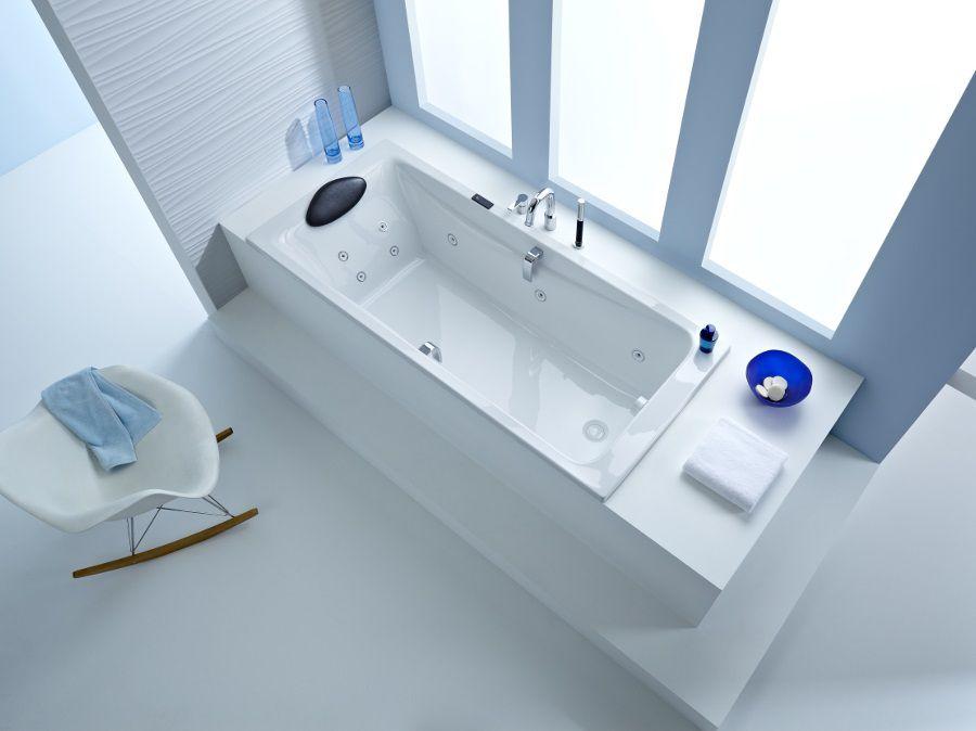 Une baignoire blanche confortable avec des buses massantes et un repose-tête pour se détendre dans la salle de bains comme dans un spa