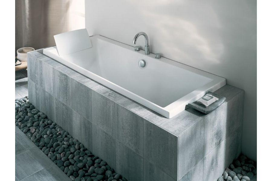 Une baignoire avec un tablier en carrelage sur-mesure gris foncé