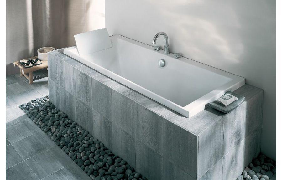 Une salle de bains avec du carrelage sombre au sol et sur le tablier de la baignoire