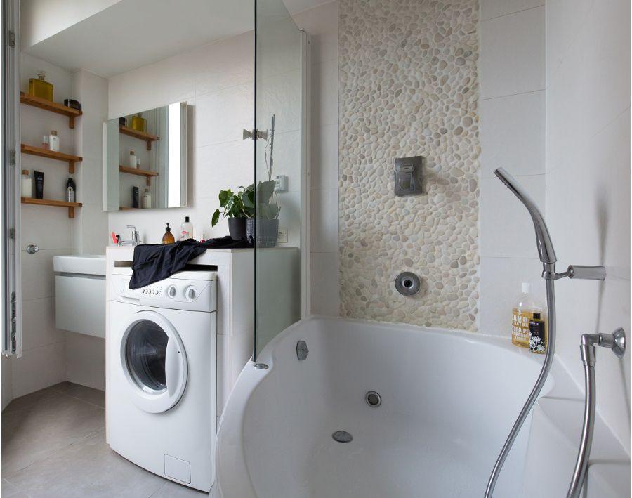 Une baignoire douche avec une paroi fixe transparente et pratique dans une petite salle de bains